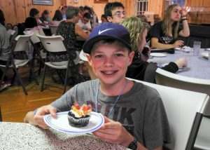 Child with allergies enjoying an allergy-friendly cupcake at Camp Blue Spruce